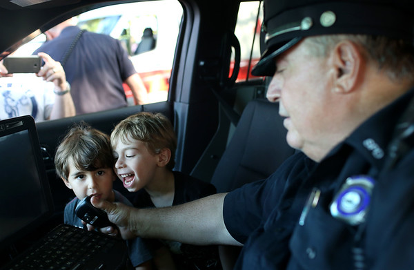 HADLEY GREEN/Staff photo<br /> Brothers Hudson and Joseph Goldberg, of Salem, have fun testing out policeman William Jennings' radio microphone at the Salem National Night Out on the Salem Common. 8/01/17