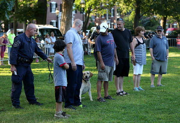 HADLEY GREEN/Staff photo<br /> People volunteered to take part in a K-9 demonstration, led by local policemen, at the Salem National Night Out on the Salem Common. Here, a K-9 sniffs participants for narcotics. 8/01/17