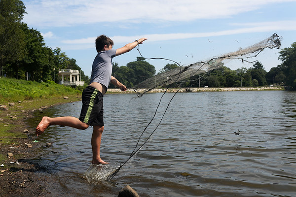 HADLEY GREEN/Staff photo<br /> On the hunt for carp and redear sunfish, Aidan Donahue throws a cast net at Mill Pond in Danvers.<br /> <br /> 07/31/2018