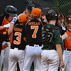 CARL RUSSO/staff photo. Beverly players surround Ryden Frost as he crosses home plate after hitting a home run. Beverly defeated Manchester Essex in Little League baseball action. 7/5/2018
