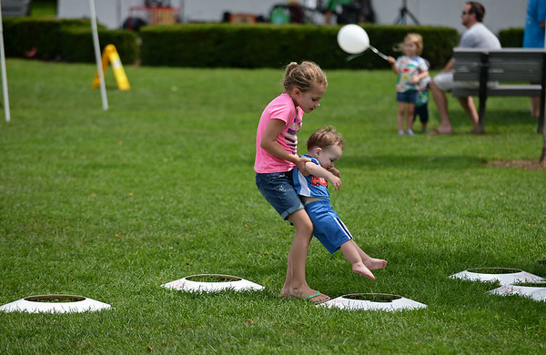 RYAN HUTTON/ Staff photo<br /> Owen Roderick, 1, gets some help from his sister Sarah, 7, navigating an obstacle course at the Beverly Homecoming in Lynch Park on Sunday.