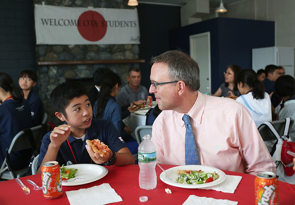 HADLEY GREEN/Staff photo<br /> Tom Daniels, director of planning and community development in Salem, speaks to Arata Yamaguchi, a student from Ota, Japan, at a pizza party hosted by Mayor Kim Driscoll at Winter Island in Salem. <br /> <br /> 07/26/2018