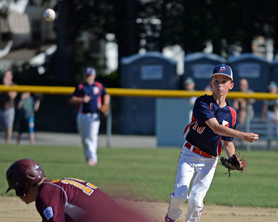 RYAN HUTTON/ Staff photo<br /> Peabody West's Thomas Fabbo fires the ball over the head of Danvers' Steve Reardon to try and make the our at first in the top of the first inning of Wednesday's Little League tournament game in Andover.