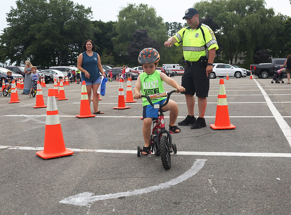HADLEY GREEN/Staff photo<br /> Gavin Cucinelli, 3, of Beverly, rides through the obstacle course while being guided by Beverly Police Officer Christopher Stanton at the Bicycle Safety Rodeo at Lynch Park.<br /> <br /> 07/30/2018