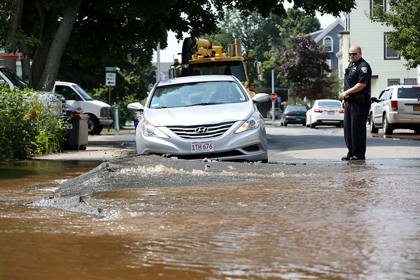 HADLEY GREEN/Staff photo<br /> A water main break on the corner of Bartlett Street and Wentzell Ave in Beverly flooded surrounding roads and sidewalks. <br /> <br /> 07/17/2018