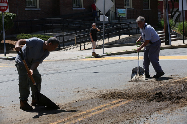 HADLEY GREEN/Staff photo<br /> People clean up manure that was dropped by a truck on Foster Street near Peabody Square on Tuesday afternoon. <br /> <br /> 07/24/2018