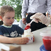 HADLEY GREEN/Staff photo<br /> Lucas Williams, 3, of Beverly, loads up his ice cream at the Beverly Homecoming Ice Cream Social at Lynch Park.<br /> <br /> 07/30/2018