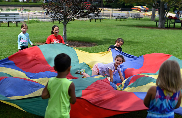 RYAN HUTTON/ Staff photo<br /> Lilly Macdonald, 6, center, plays a game of cat and mouse with other kids at the Beverly Homecoming in Lynch Park on Sunday.