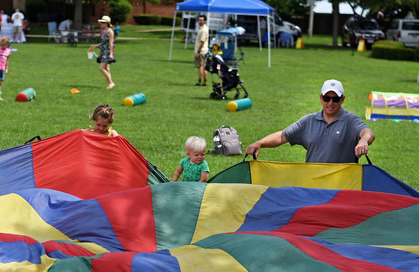 RYAN HUTTON/ Staff photo<br /> Jim Boland, right, and his son Ben, 1, center, play a parachute game along with Sadie Morris, 4, left, at the Beverly Homecoming in Lynch Park on Sunday.