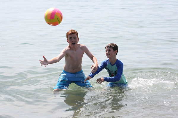 HADLEY GREEN/Staff photo<br /> Children play catch in the ocean at Devereaux Beach in Marblehead. <br /> <br /> 07/31/2018