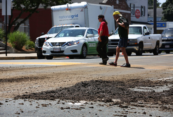 HADLEY GREEN/Staff photo<br /> People walk by a pile of manure dropped by a truck on Foster Street near Peabody Square on Tuesday afternoon. <br /> <br /> 07/24/2018
