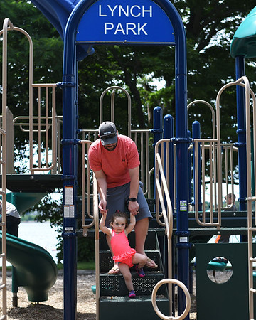 RYAN HUTTON/ Staff photo<br /> Alex Rocklein helps his daughter Evelyn, 1, climb down the jungle gym at the playground at the Beverly Homecoming in Lynch Park on Sunday.