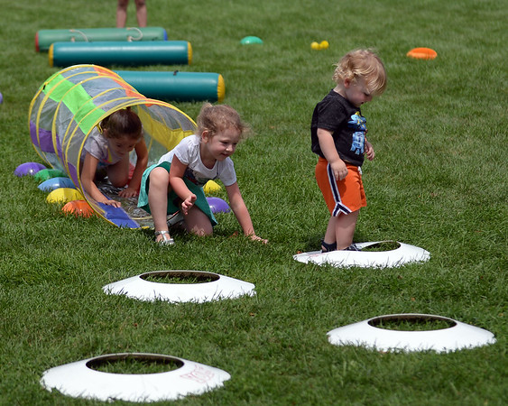 RYAN HUTTON/ Staff photo<br /> Ben Macdonald, 20 months, right, and his sister Emily, 3, left, crawl through an obstacle course at the Beverly Homecoming in Lynch Park on Sunday.