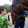 HADLEY GREEN/Staff photo<br /> Lamari Flanagan, 9, of Beverly, visits with a Massachusetts State Police horse before the Beverly Homecoming Ice Cream Social at Lynch Park.<br /> <br /> 07/30/2018