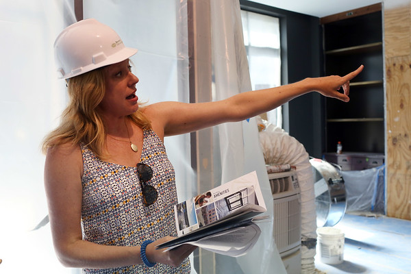 HADLEY GREEN/Staff photo<br /> Sarah Barnat, president of Barnat Development, points out amenities in the lobby of the new Holmes Beverly apartment complex on Rantoul Street. <br /> <br /> 07/18/2018