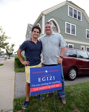 """RYAN HUTTON/ Staff photo<br /> Vinny Egizi, right, stands with his son Marco, left, with the sign that Marco got his dad for his birthday recently. It reads; """"Vinny Egizi, I'm not running for anything, I just wanted my own sign."""""""