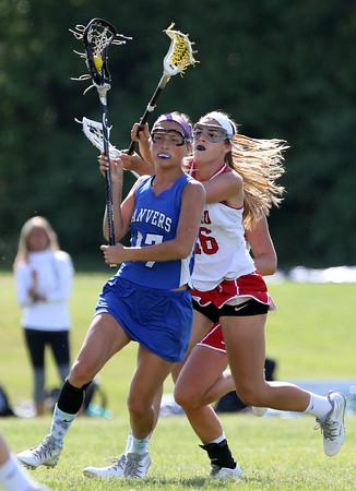 DAVID LE/Staff photo. Danvers senior Abigail Armstrong (17) tries to protect the ball as Masco junior Grace Fahey (16) tries to knock the ball loose from behind. 6/2/16.