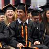 DAVID LE/Staff photo. Beverly High School graduates Ryan Anderson, Ahmad Alshrafi, and Tiana Allen-Rodriguez, smile while listening to Salutatorian Samuel Peterson's speech on Sunday afternoon. 6/5/16.