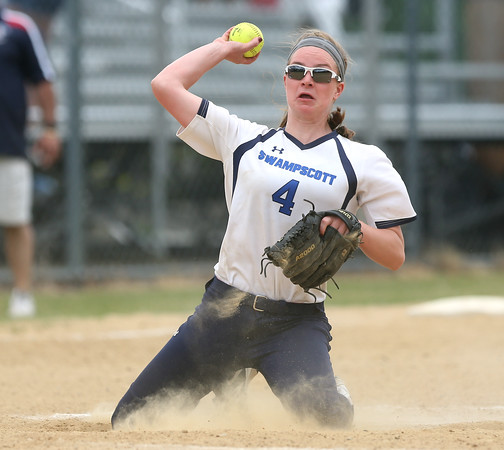 DAVID LE/Staff photo. Swampscott junior captain Hannah Leahy tries to fire a throw to first from her knees after a hard hit ball ricocheted off her shin. 6/12/16.