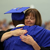 DAVID LE/Staff photo. Danvers High School principal Susan Ambrozavitch gives a heartfelt hug to graduate Tre Crittendon after he delivered the Keynote Address on Saturday afternoon. 6/11/16.