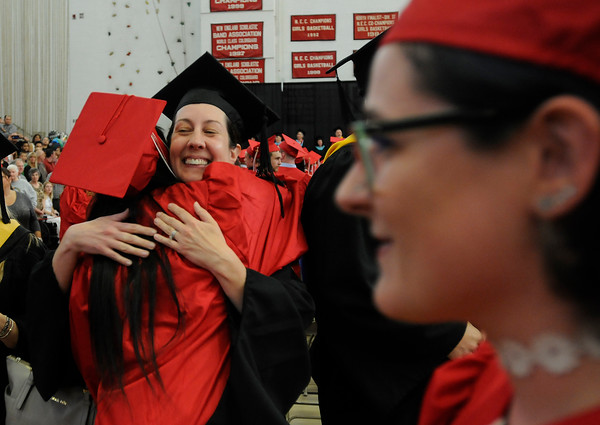 PAUL BILODEAU/Staff photo. Salem High councilor Bonnie Chesley, facing camera,  hugs a student as they enter during Salem High School's graduation ceremony in the high school's field house.