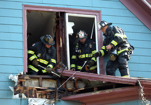 DAVID LE/Staff photo. Salem firefighters pry off the roof outside a small balcony off the third floor window of 38 Harbor Ave in Salem after dousing a fire that broke out. 6/24/16.