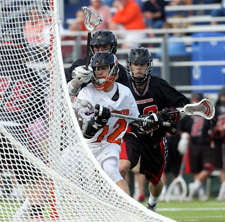 DAVID LE/Staff photo. Beverly senior attack Hunter Spencer forces his way to the net and bears down on Winchester freshman Harris Carpini, left. 6/10/16.