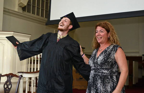 RYAN HUTTON/ Staff photo<br /> Northshore Recovery High School graduate John Jerome mugs for the cameras after getting his diploma from school director Michelle Lipinski at the school's commencement ceremony at the Second Congregational Church in Beverly on Wednesday night.