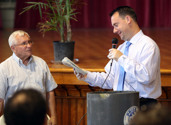 DAVID LE/Staff photo. Peabody Mayor Ted Bettencourt, right, reads the front page of an article in a newspaper packed into a time capsule from 1989. 6/29/16.