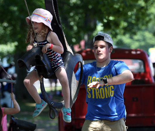 DAVID LE/Staff photo. Fifteen-year-old John Collins, of Lynnfield, pushes his sister Vivienne, 3, on a saddle swing at the annual Strawberry Festival held at Connors Farm in Danvers as part of the Danvers Family Festival. 6/18/16.