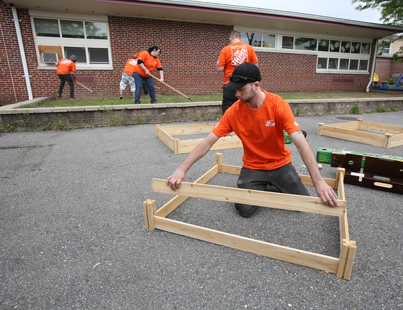 KEN YUSZKUS/Staff photo.  In the foreground, Travis Skidgell of Peabody builds one of the raised cedar beds that will be used in the garden in the background that his co-workers are preparing at Riverside School in Danvers.        06/02/16