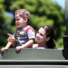 DAVID LE/Staff photo. Enzo Arias, 3, of Salem, smiles wide while being held out the roof of a NEMLEC Swat Team vehicle, by his mom Cella, at the annual Touch-a-Truck event held at the Liberty Tree Mall in Danvers as part of the Danvers Family Festival. 6/18/16.