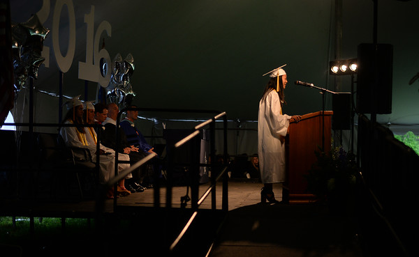 PAUL BILODEAU/Staff photo. Valedictorian Jeanine Zheng delivers her address during Hamilton-Wenham Regional High School's graduation ceremony in a tent on the football field at the school.