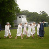 PAUL BILODEAU/Staff photo. A group of soon to be graduates make their way to their ceremony in the rain during Hamilton-Wenham Regional High School's graduation ceremony in a tent on the football field at the school.