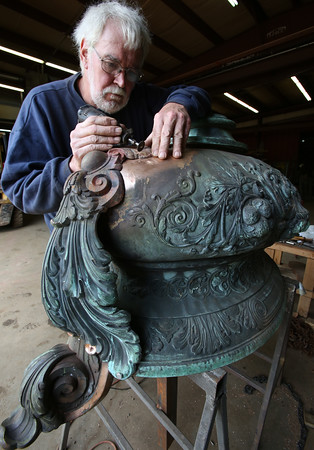 KEN YUSZKUS/Staff photo.    Al Murphy is blending the rivets on the handles of the George A. Peabody urn.     06/13/16
