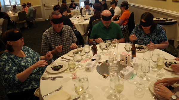 DAVID LE/Staff photo. A table full of blindfolded diners taste their second course of a four course meal at Dinner in the Dark held at the Hawthorne Hotel. 6/8/16.