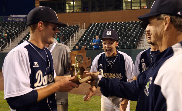 DAVID LE/Staff photo. Danvers senior captains Andrew Olszak, left, and Danny Lynch, excitedly take the D2 North Championship trophy from head coach Roger Day after beating Reading 9-4 at LeLacheur Park in Lowell on Sunday evening. 6/11/16.