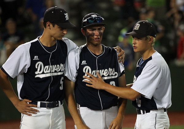 DAVID LE/Staff photo. Danvers senior captain Tim Unczur, center, is consoled by teammates Zach Turner, left, and Ryan McGinnis, right, after the Falcons lost in the bottom of the 8th inning on a walk-off squeeze bunt. 6/15/16.