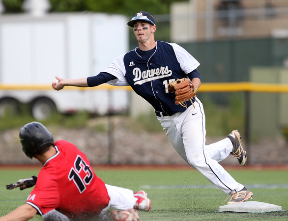 DAVID LE/Staff photo. Danvers senior shortstop Andrew Olszak steps around North Andover senior Joseph Kramer (13) as he fires to first to complete a Falcon 6-3 double play. 6/9/16.