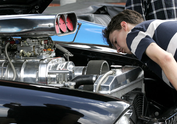 KEN YUSZKUS/Staff photo.    Dylan Ruelle of Salem takes a closeup look at the engine in a 1955 Chevy at the antique car show held in Peabody.     06/12/16