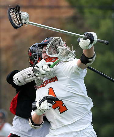 DAVID LE/Staff photo. Beverly senior Ryan Garrity gets wrapped up with a stick around the chest while trying to move the ball upfield against Winchester on Friday afternoon. 6/10/16.