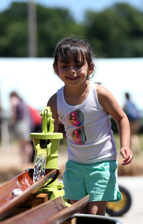 DAVID LE/Staff photo. Five-year-old Chanel Goncalves, of Peabody, pumps water to race a plastic soccer ball to the other end of a water pump game at the annual Strawberry Festival held at Connors Farm in Danvers as part of the Danvers Family Festival. 6/18/16.