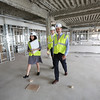 KEN YUSZKUS/Staff photo.   From left, vice president of marketing & sales Liz Speranzella, leasing associate Aaron Smith, and vice president/general manager Stephen Drohosky walk through the Cummings Center's new condo complex under construction, Elliott Landing.       06/09/16