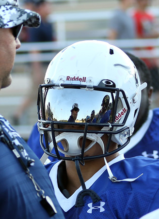 DAVID LE/Staff photo. The reflection of Peabody head coach Mark Bettencourt is seen reflected in the visor of Assumption bound star running back Dougie Santos on the sidelines of the Agganis football game on Thursday evening. 6/30/16.