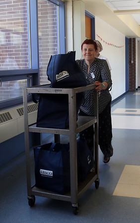 DAVID LE/Staff photo. Linda Carvaggio, longtime Beverly Bookmobile Librarian pushes a cart of books down the hallway at the Hannah School on Brimbal Ave. Carvaggio is retiring from driving the Bookmobile after over twenty years. 6/21/16.