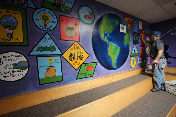 KEN YUSZKUS/Staff photo.     Phillip Coleman touches up parts of the mural at the Centerville School in Beverly.     06/15/16