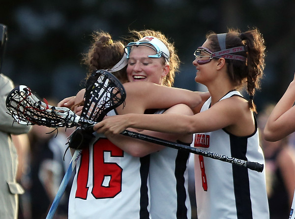 DAVID LE/Staff photo. Marblehead senior captain Kylie Cronin, center, gets hugged by senior Kaitlyn Bernato, left, and sophomore Carolyn Arthur, right, after the Magicians captured the D2 North Title over Ipswich. 6/9/16.