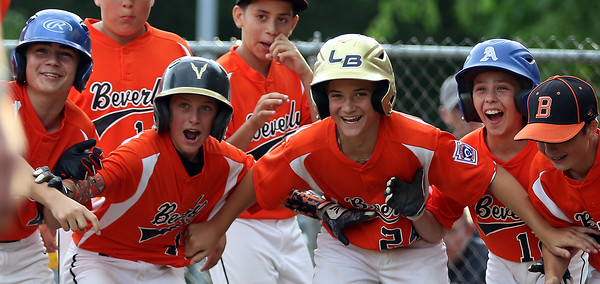 DAVID LE/Staff photo. Beverly players have to hold each other back in excitement while waiting for teammate Joey Loreti after he launched a 3-run home run to dead center field against Danvers. 6/29/16.