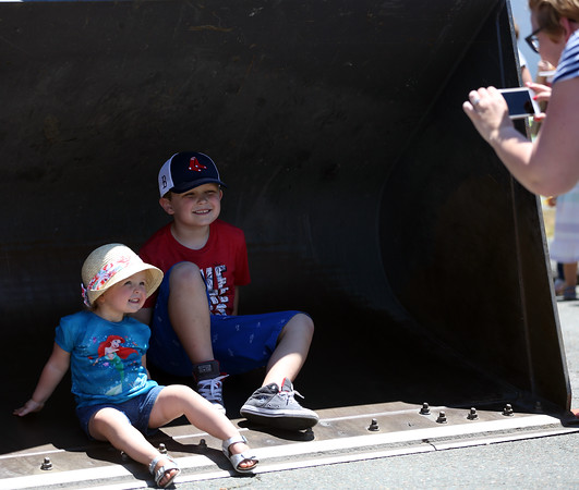DAVID LE/Staff photo. Siblings Noreen, 2, and Jake Merry, 6, pose for a photo in the bucket of a front loader for their mom, Kelly, at the annual Touch-a-Truck event held at the Liberty Tree Mall in Danvers as part of the Danvers Family Festival. 6/18/16.