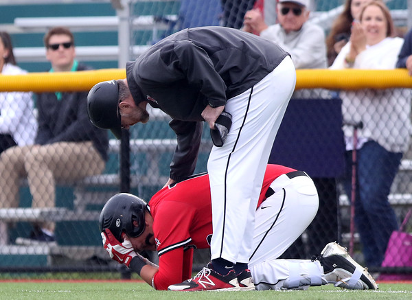 DAVID LE/Staff photo. North Andover senior Joseph Bramanti is consoled by his first base coach after he made the final out of the Scarlet Knights 6-3 loss to Danvers on Thursday afternoon in the D2 North semifinal. 6/9/16.